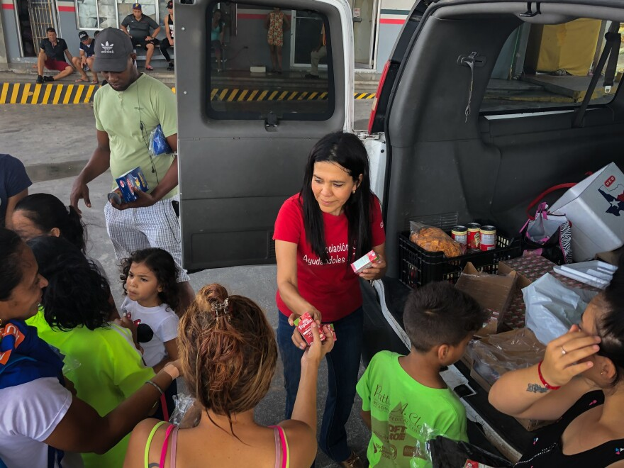 Glady Caña, an unemployed lawyer, hands out apple juice to asylum-seekers at the border in Matamoros.