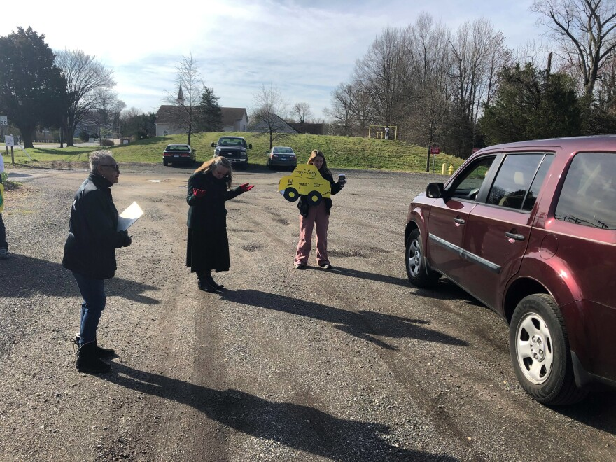 Lay ministers Darlene Washington (from left) and Jackie Waymire and Pastor Faith Wilkerson pray with a couple in the Centenary Methodist Church parking lot in Shady Side, Md.