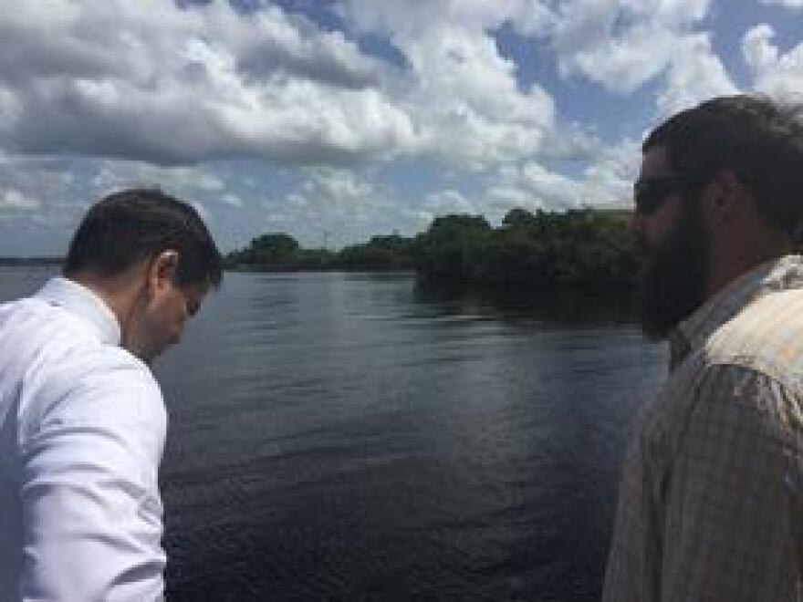 U.S. Sen. Marco Rubio looks at the brown waters of the Caloosahatchee while speaking with Daniel Andrews. Andrews is part of the advocacy group Captains for Clean Water.