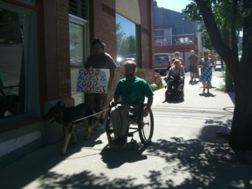 """A man in a wheelchair goes down a sidewalk next to a dog and person holding a sign that says """"Good Access is Good Business""""."""