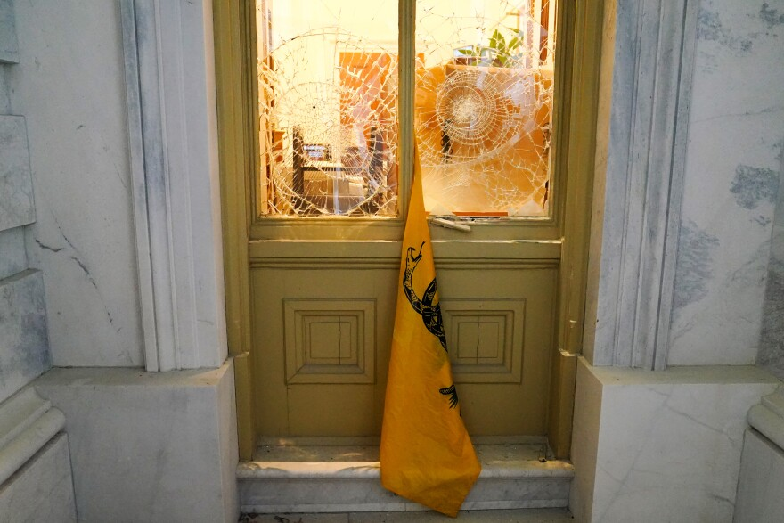 A flag hangs between broken windows outside the U.S. Capitol