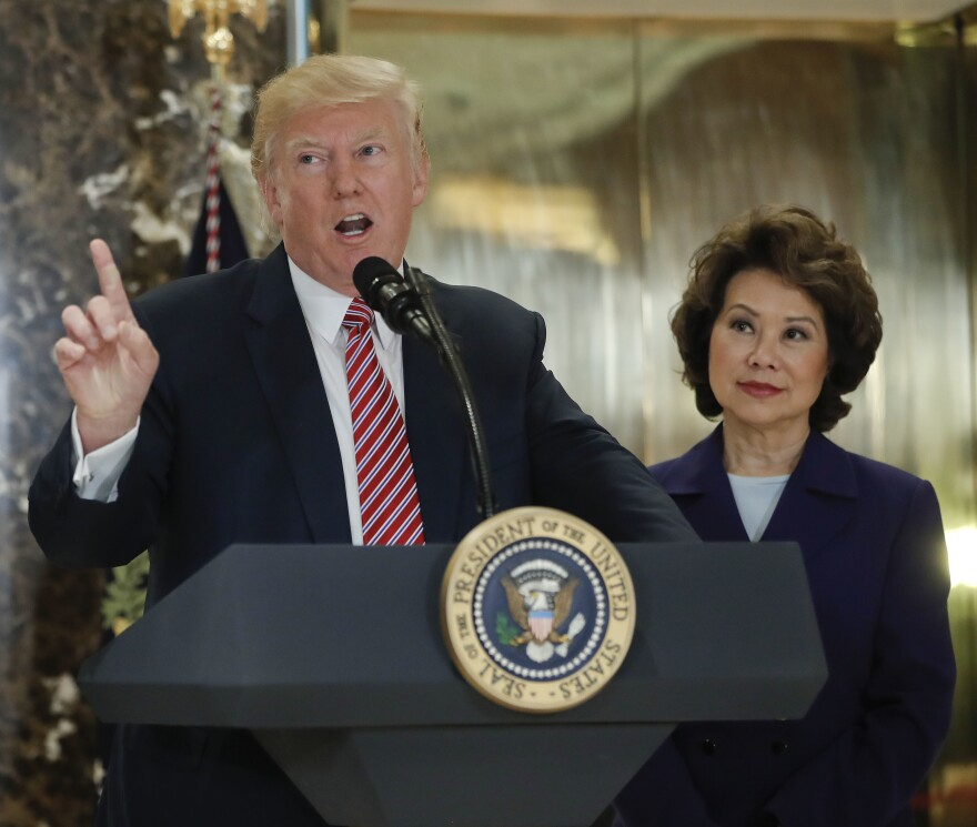 "Mitch McConnell's wife, Secretary of Transportation Elaine Chao, stands behind President Trump at a news conference in August 2017. At that news conference, Trump delivered widely condemned remarks describing ""very fine people on both sides"" of a deadly white supremacist rally in Charlottesville, Va."