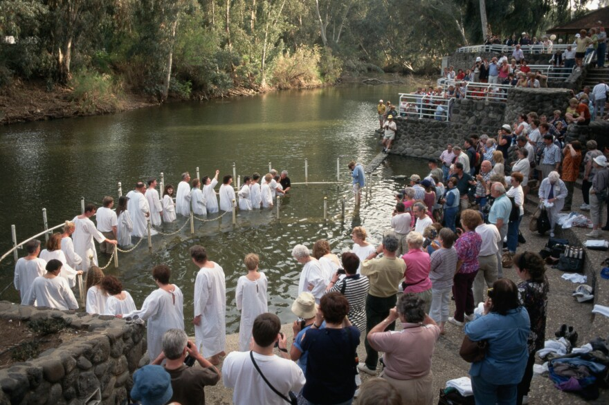 Pilgrims gather on the banks of the Jordan River at Galilee for baptisms. Israeli authorities are eager to accommodate tourists' interest in ancient Israel, according to author Daniel Hummel.