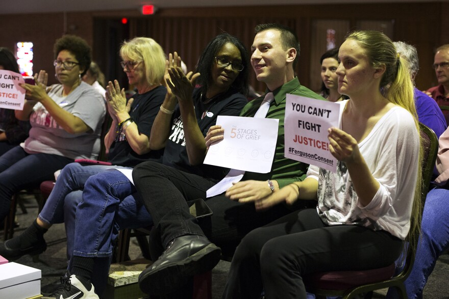 Ferguson activists and residents listen to public comments before the city council's vote on the consent decree.