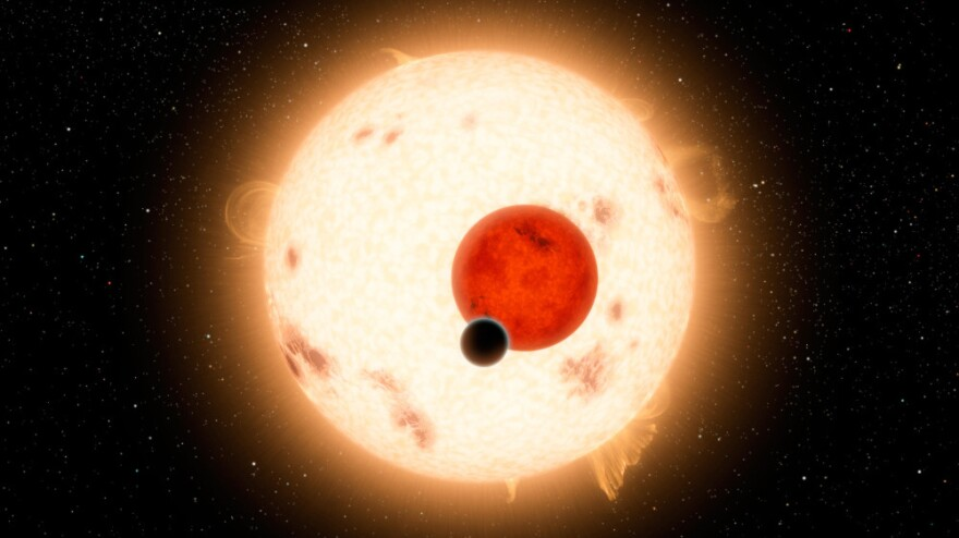 NASA's Kepler mission has discovered a planet that circles two stars instead of one. The planet, shown as the black dot in this artist's illustration, is similar to Saturn, though it is more dense and travels in a 229-day circular orbit around its two stars.