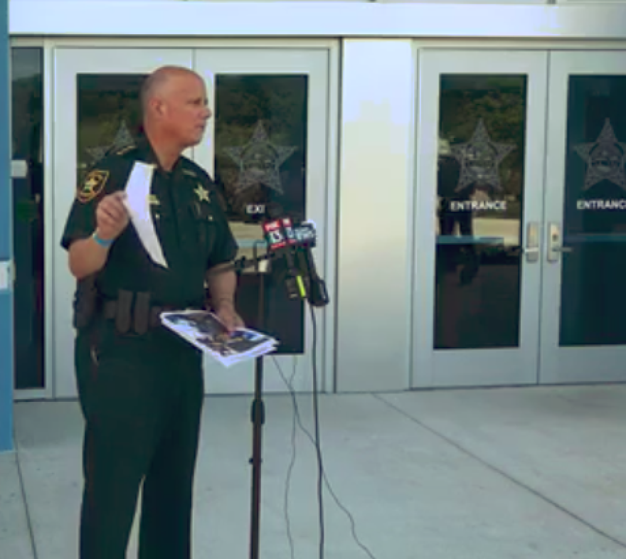 sheriff stands in front of microphones, showing photos to unseen audience