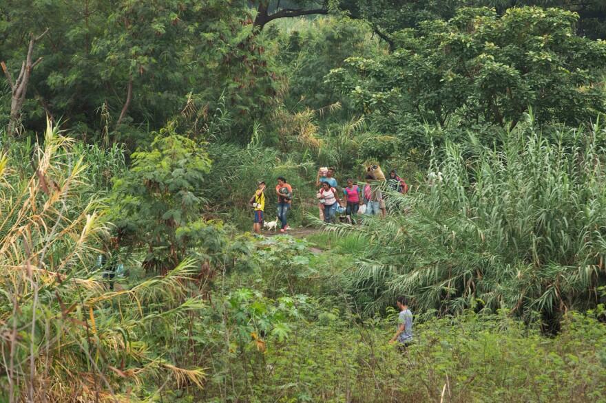 People walk into Colombia through an illegal crossing near the Simón Bolívar bridge.