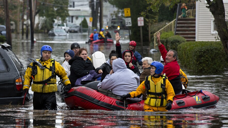 First responders rescue flood-stranded people from a sodden neighborhood in Little Ferry, N.J., on Tuesday.