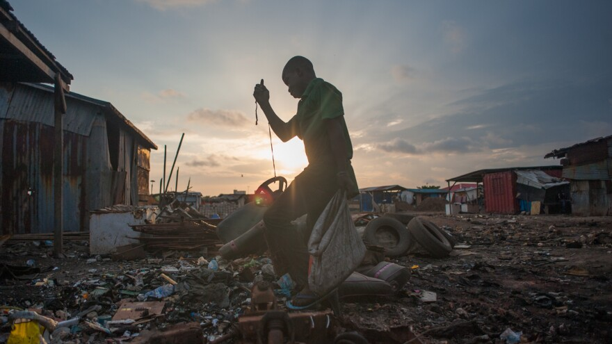 Kwesi Bido walks through part of the electronic waste dump at Agbogbloshie, in Accra, Ghana. Some of the digital waste comes from developed countries, where it was supposed to be recycled — but instead was illegally shipped here to be dumped.