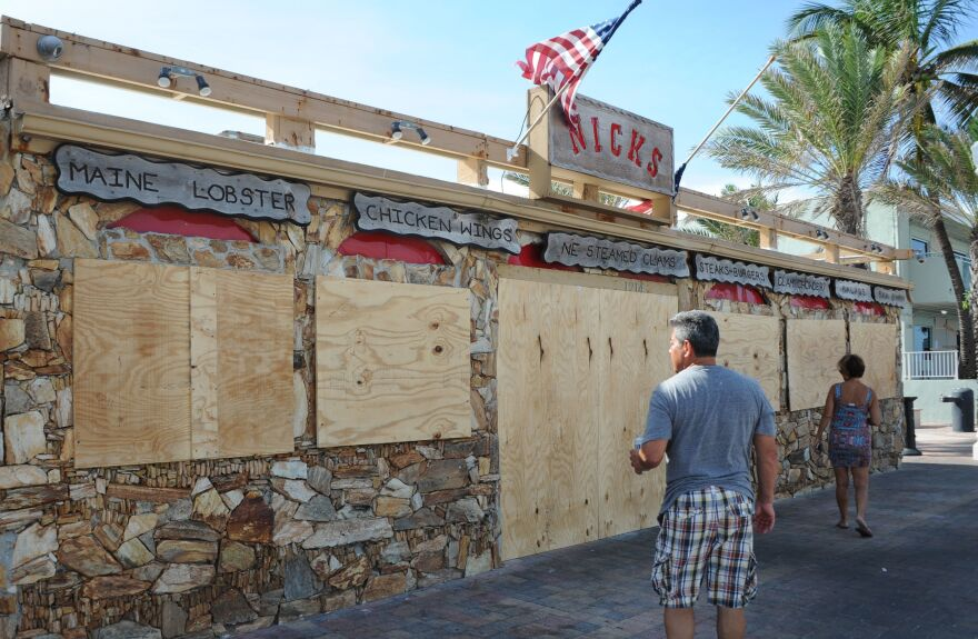 Tourists walk past a restaurant, closed in preparation for hurricane Irma, in Fort Lauderdale, Fla., on Sept. 7. The Bureau of Labor Statistics says a drop in U.S. jobs in September was likely reflecting the impact of hurricanes on workers — particularly restaurant employees who aren't paid if they aren't on the job.