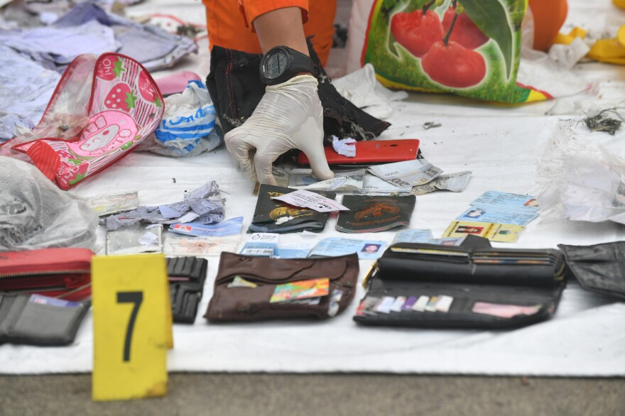 Indonesian search and rescue members place new evidence of personal items from the Lion Air flight JT610 at the Jakarta port on Tuesday.