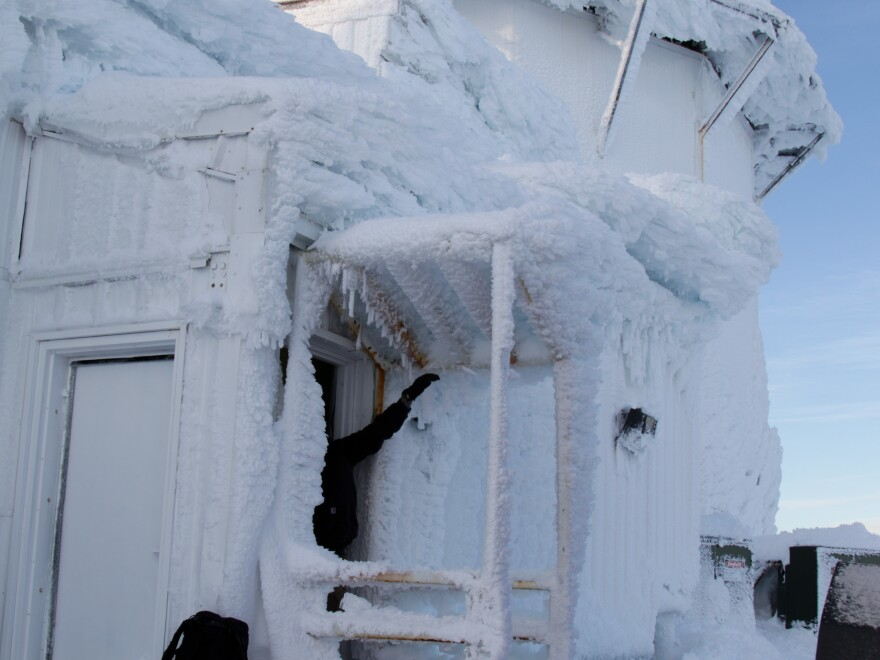 A contractor clears ice from the door of the long-range radar building at Tin City.