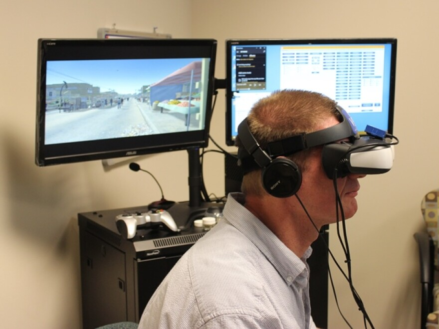 Therapist Keith Smith demonstrates virtual reality equipment at the University of Central Florida. Smith uses virtual reality to help treat veterans' post traumatic stress disorder.