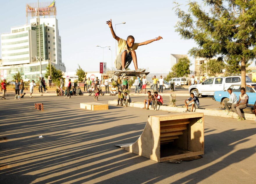 Henok launches off a homemade quarterpipe ramp at a parking lot.