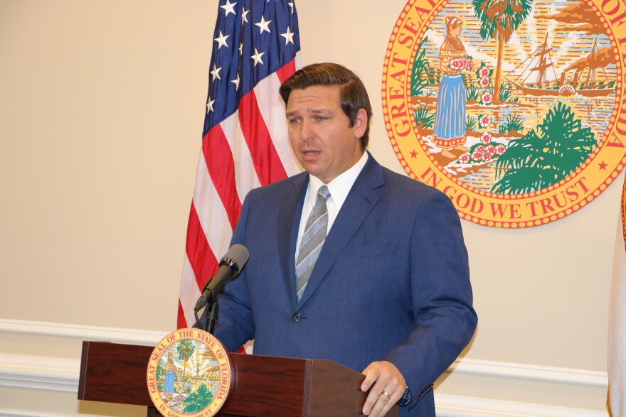 Governor Ron DeSantis speaking at a podium in his Press Office