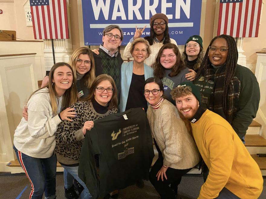A group of students huddle around Elizabeth Warren