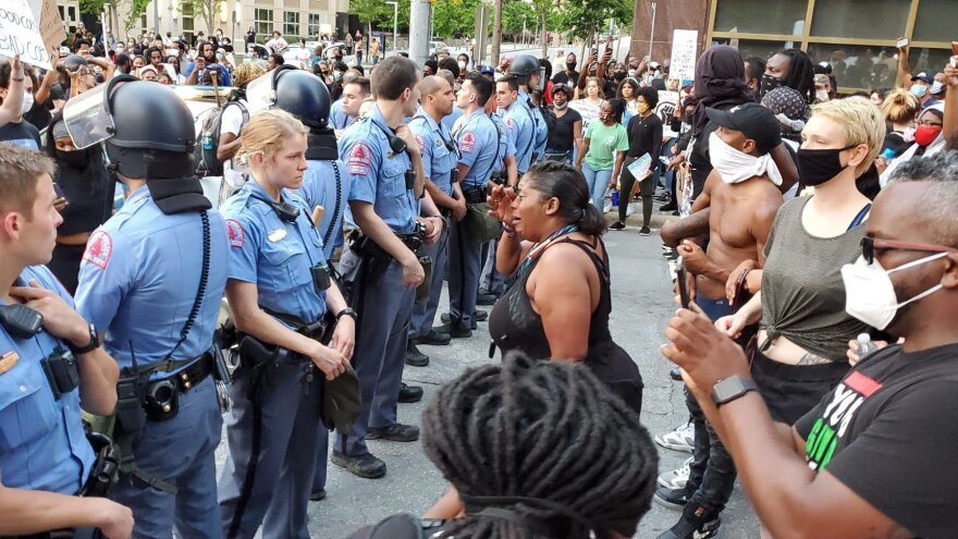 Police officers stand in a line amid protesters in Raleigh, N.C.