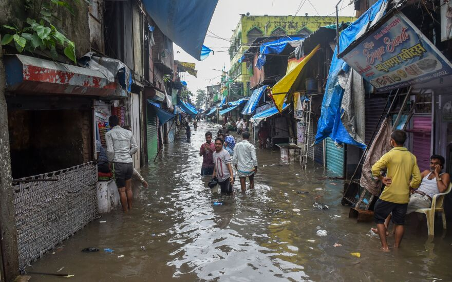 Residents wade in a flooded street after heavy monsoon rains in Mumbai on August 4, 2019.