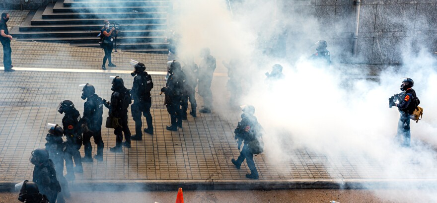 Police disperse tear gas in downtown Raleigh during a protest on May 30, 2020 to call for justice in the death of George Floyd, a black man who died while in police custody in Minneapolis earlier in the week.
