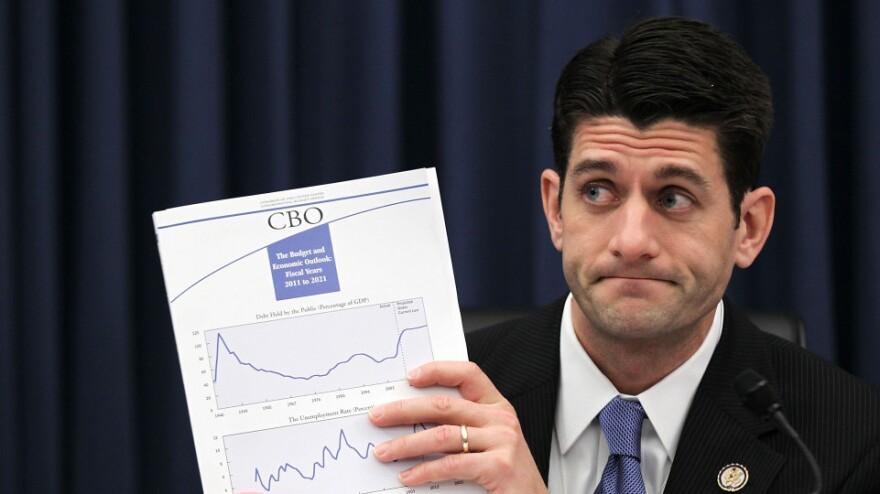 At a House Budget Committee hearing in February, Rep. Paul Ryan (R-WI) holds up a Congressional Budget Office report on the federal budget.