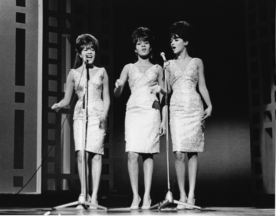 "The Ronettes (left to right: Veronica Bennett, Estelle Bennett an Nedra Talley) on stage in 1963, the year they signed with Phil Spector and recorded and released ""Be My Baby."""