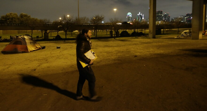 Man walking with clip board in hand with tent and Dallas skyline in the background.
