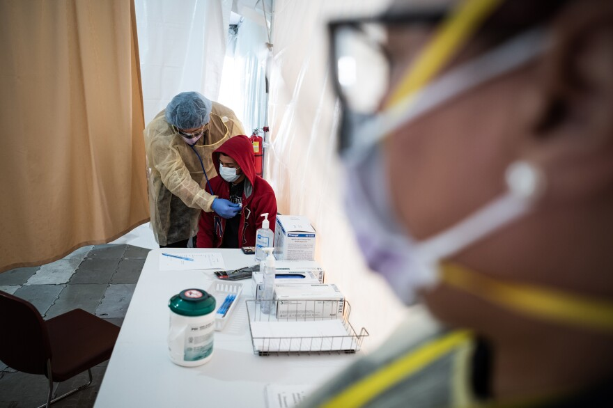 A doctor examines Juan Vasquez as part of a COVID-19 check inside a testing tent outside the emergency department at St. Barnabas Hospital in New York City last week.