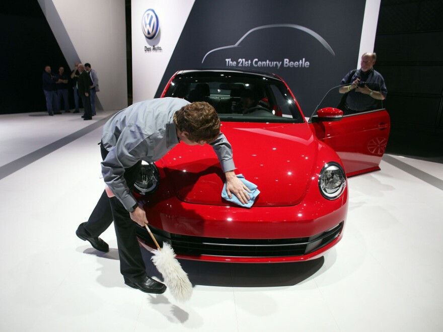 An auto detailer polishes the new 2012 Volkswagen Beetle on the floor of the New York International Auto Show.