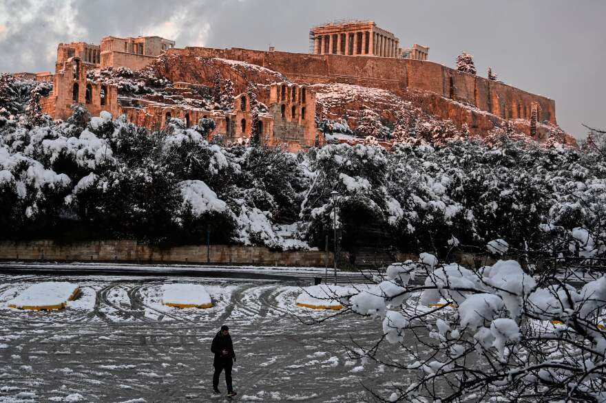 The setting sun illuminates the ancient Acropolis in Athens, Greece, after a rare heavy snowfall in the city on Tuesday.