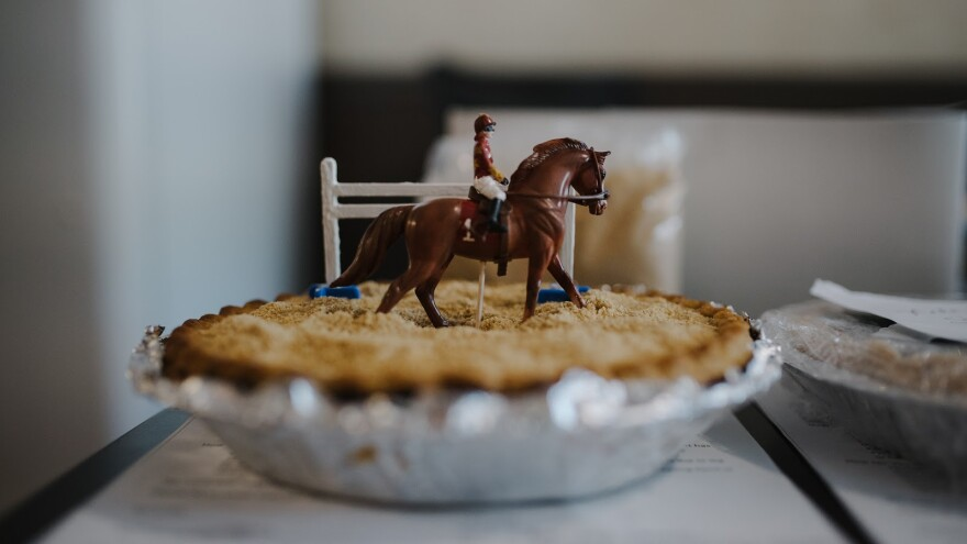 A pie with a toy horse on top.