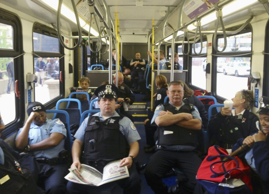 Chicago police officers sit in a bus outside the Boeing headquarters in Chicago on Monday.