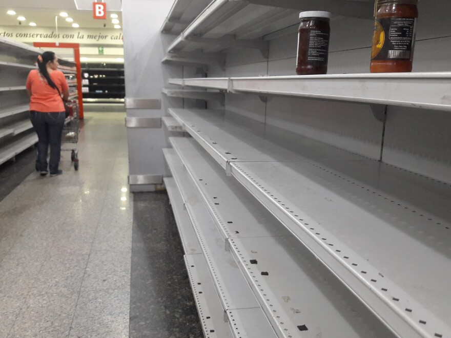 A woman walks between the empty shelves of a supermarket in Caracas on January 11, 2018.