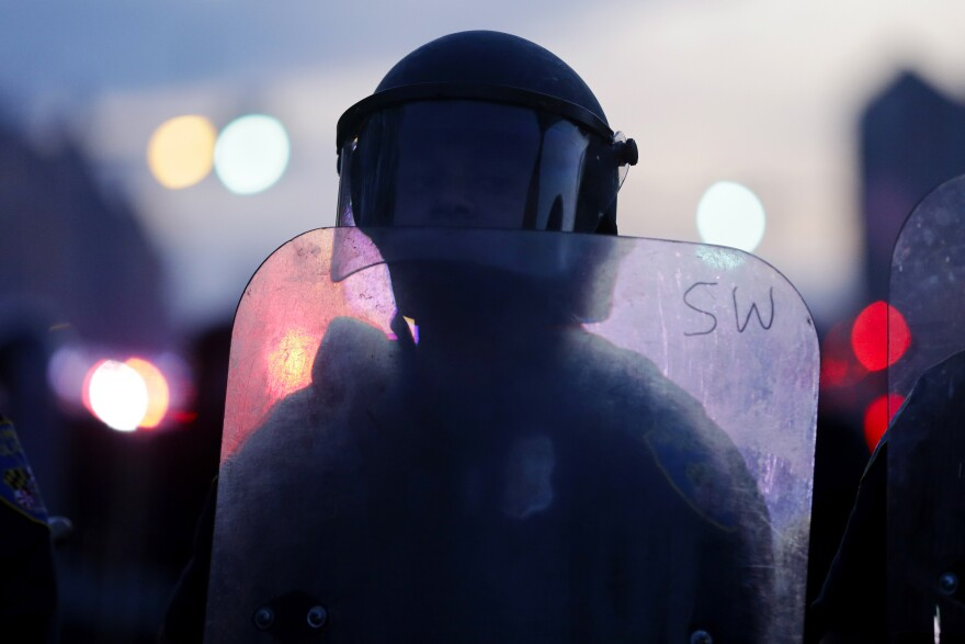 A police officer stands guard in riot gear after violence erupted in Baltimore.