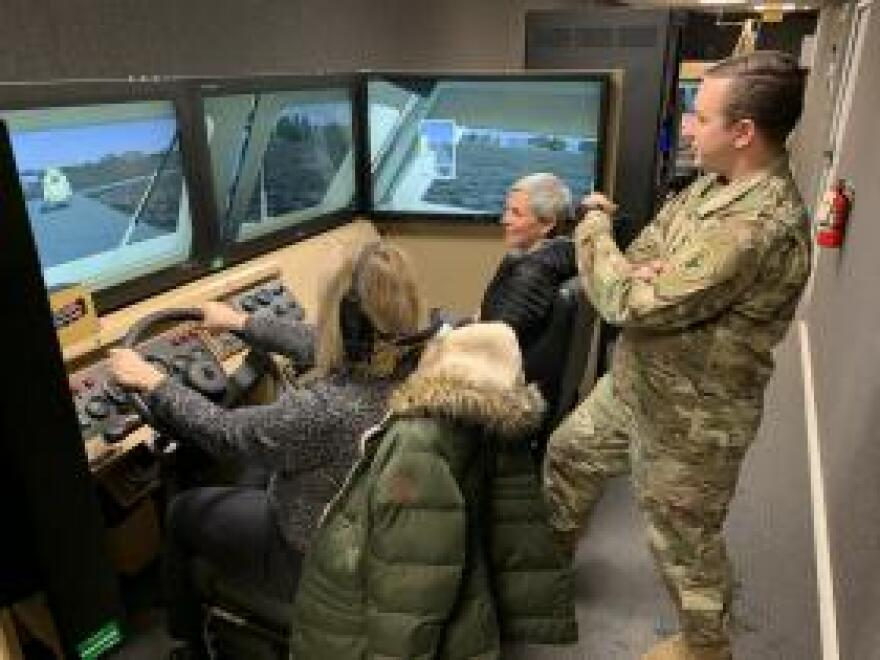 Teachers Kate Bridgman (left) and Lisa Jolstad of Cheyenne Mountain High School in Colorado, sit in a driving simulator at Fort Carson while Army Capt. Wes Barber looks on.