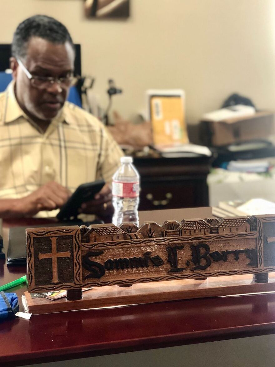 "A wooden engraved plaque that reads ""Sammie L. Berry"" inside his office at Dallas West Church of Christ."