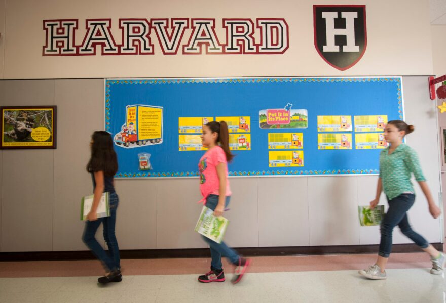 Students at Lyons Elementary school pass by logos for major universities on their way to lunch in this archive photo.