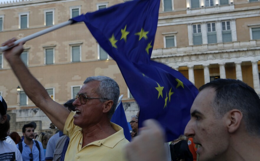 The economic crisis in Greece has divided the country. Here, a pro-euro demonstrator shouts slogans as he holds a European Union flag in front of the Greek Parliament during a rally in Athens on Thursday.