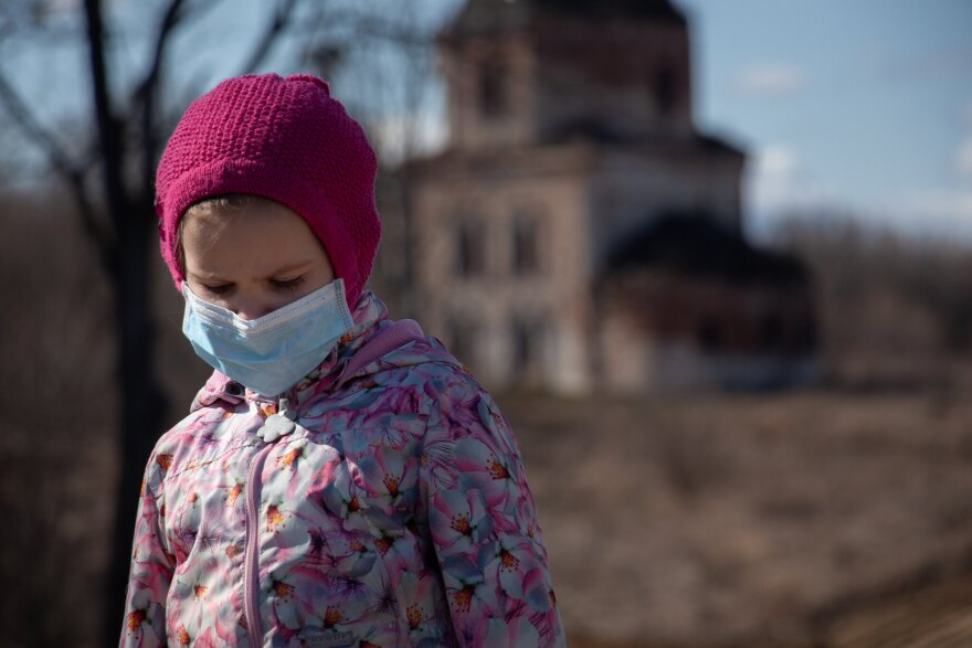 A photo of a little girl in a pink jacket and hat, also wearing a face mask.