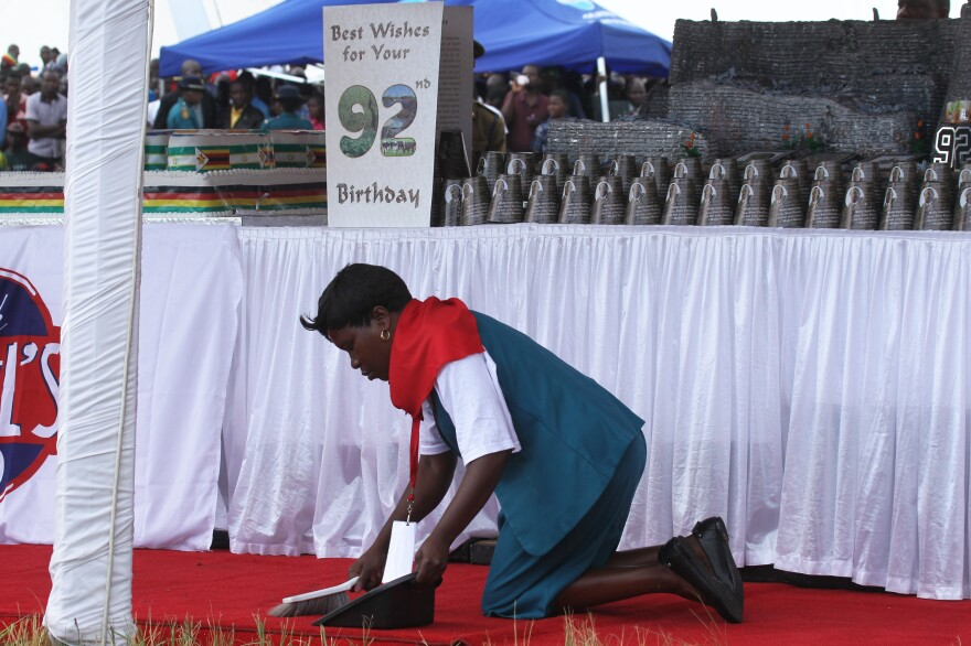 A woman cleans the carpet during birthday celebrations for Zimbabwean President Robert Mugabe on Saturday in Masvingo, about 300 kilometres south of Harare, Zimbabwe.