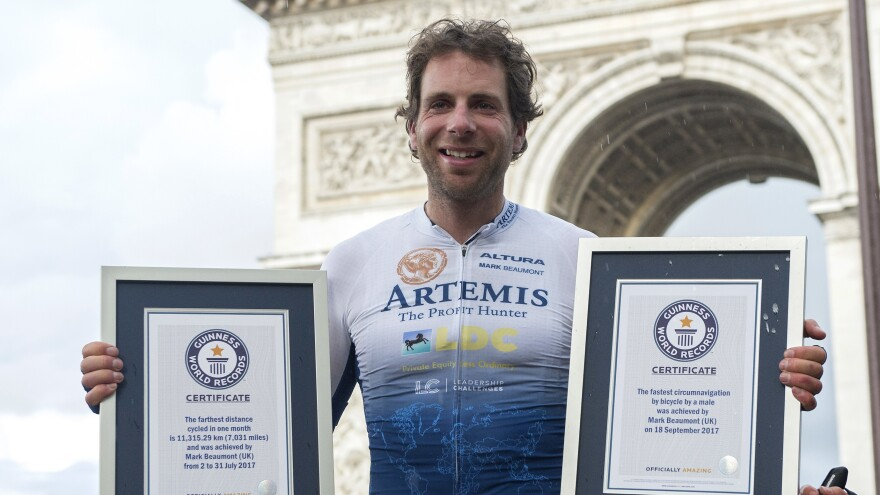 Mark Beaumont poses with his Guinness World Records in Paris Monday after cycling for 79 days around the world.