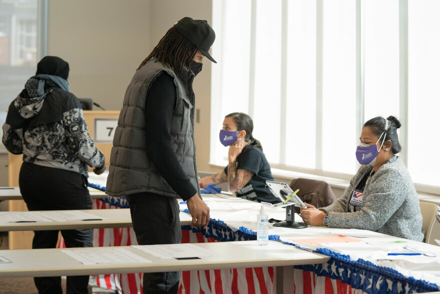 Poll workers help voters get ready to cast their ballots at on Nov. 3, 2020 in Atlanta. State lawmakers are now considering legislation that could roll back some laws that made it easy for voters to cast ballots by mail.