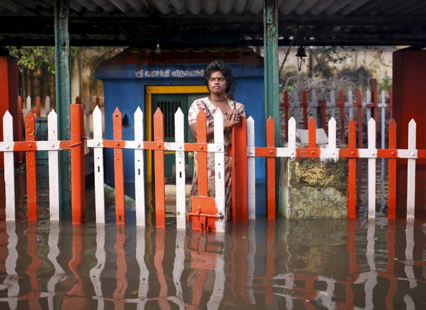 A woman stands outside a submerged temple on Friday.