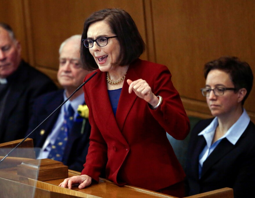 Oregon Gov. Kate Brown, D, center, recently signed a bill into law that would require insurers in the state to cover reproductive health services.
