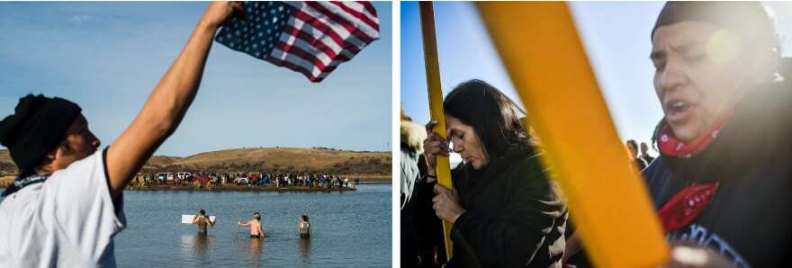 Protesters (left) wade into the Cannonball River as others (right) pray and hold flags while marching across a wooden pedestrian bridge across a creek north of the main protest camp near the Standing Rock Sioux Reservation.