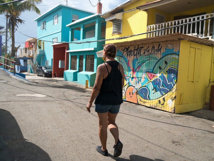 """Carmen Lourdes Lopez, 58, walks in the La Perla neighborhood. Over the summer, she was giving """"Despacito"""" tours to people visiting Puerto Rico."""