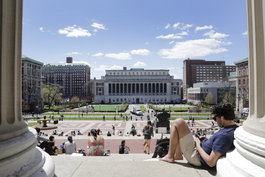 Students sunbathe on the steps of Columbia University's Low Memorial Library, April 29, 2015 in New York. (AP Photo/Mark Lennihan)