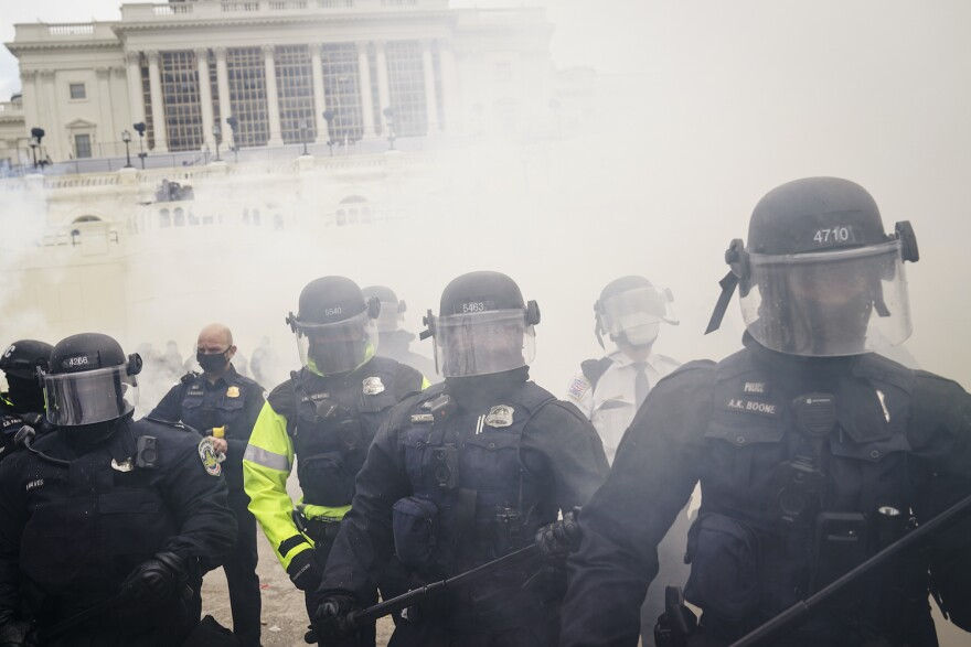 Supporters loyal to President Donald Trump clash with authorities before successfully breaching the Capitol building during a riot on the grounds, Wednesday, Jan. 6, 2021. (John Minchillo/AP)