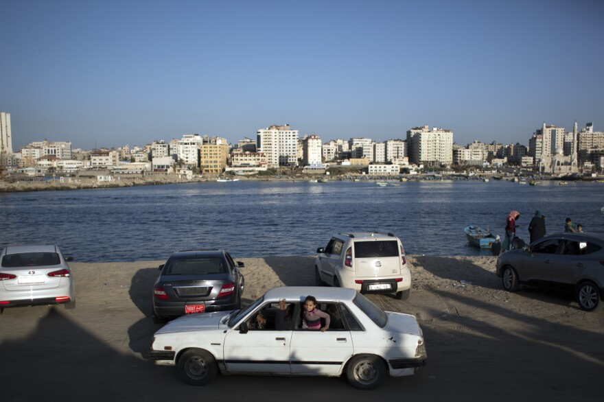 A girl appears from the window of a car driving along the beach in Gaza City.