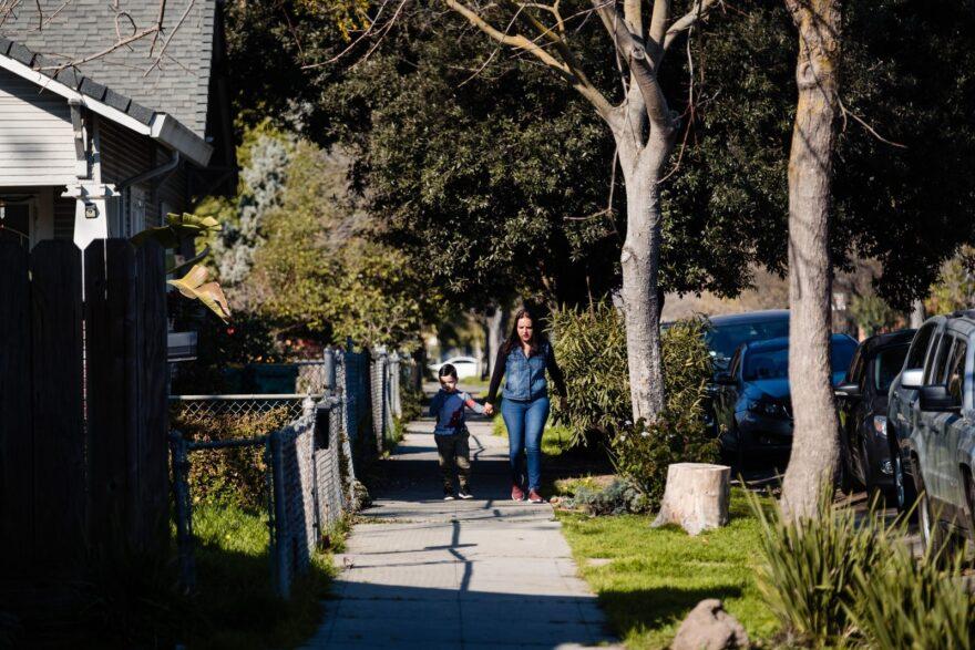 A mother and son walk through Stockton, California.