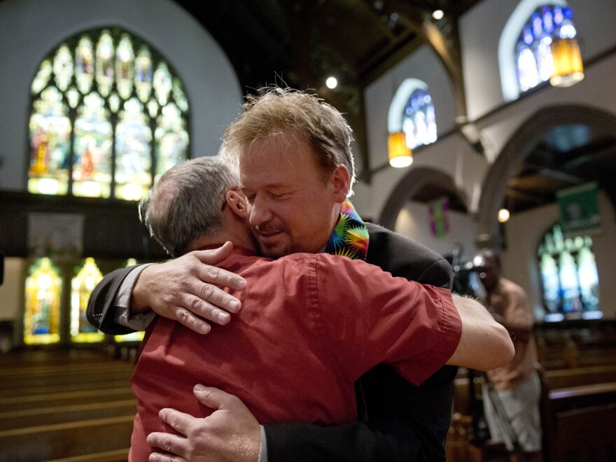 United Methodist minister Frank Schaefer (right) hugs the Rev. David Wesley Brown after a news conference Tuesday at First United Methodist Church of Germantown, Pa. Schaefer was reinstated by the church after being defrocked for presiding over his son's same-sex wedding ceremony.